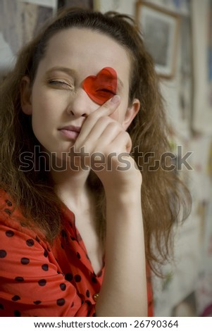 portrait of young attractive girl looking through the plastic heart