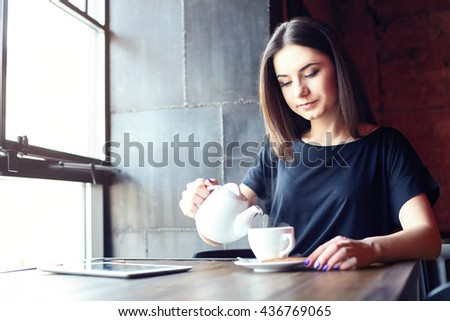 Portrait of young attractive girl pouring tea in coffee shop while sitting alone in cafe during free time. Lifestyle. - stock photo