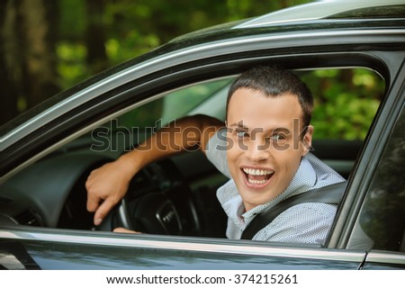 Portrait of young attractive handsome brunette man driving car and greeting somebody.