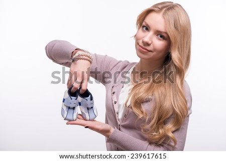 Portrait of young attractive happy Caucasian woman with long fair hair smiling and holding baby shoes, isolated on white background, baby expectation concept - stock photo