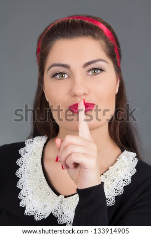 portrait of young attractive maid with finger on her red lips