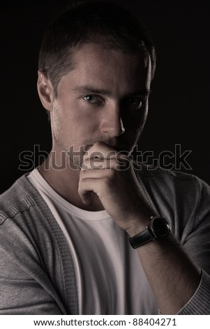 Portrait of young attractive man on black. Low key - stock photo