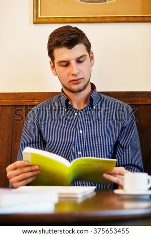 Portrait of young attractive man sitting in cafe and reading book. - stock photo