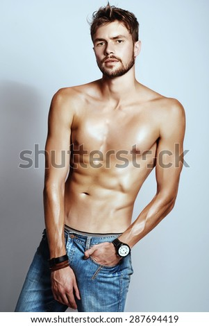 Portrait of young attractive man with a naked torso in the studio - stock photo