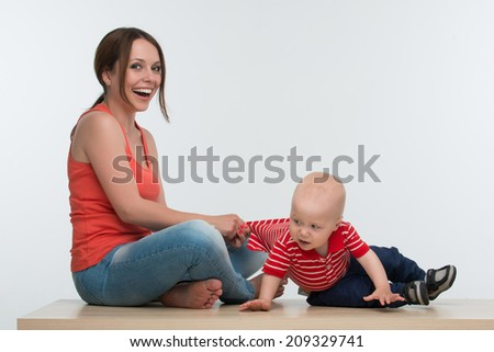 Portrait of young attractive mother catching her active little toddler kid, isolated on white - stock photo