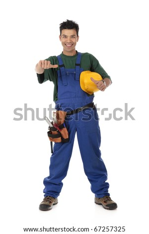 Portrait of young attractive Nepalese carpenter with a thumb-up, wearing a blue overall, tool belt and holding a  yellow helmet . Studio shot. White background. - stock photo