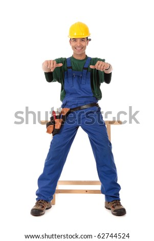 Portrait of young attractive Nepalese carpenter with thumbs-up, wearing a blue overall, tool belt and helmet, sitting and smiling . Studio shot. White background. - stock photo