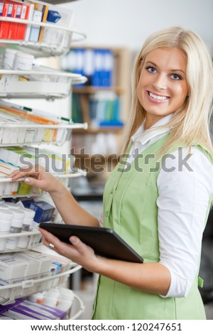 Portrait of young attractive pharmacist using digital tablet to fill order - stock photo