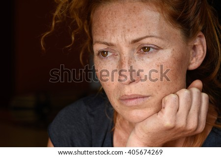 portrait of young attractive red hair woman without makeup holding chin with hand thinking about problems and looking away close up - stock photo