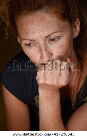 portrait of young attractive red hair woman without makeup holding chin with hand thinking about problems and looking down close up - stock photo