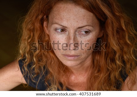 portrait of young attractive red hair woman without makeup looking away and thinking about problems close up - stock photo