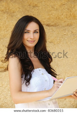 Portrait of young attractive smiling brunette woman working with pad and pen against beige background. - stock photo