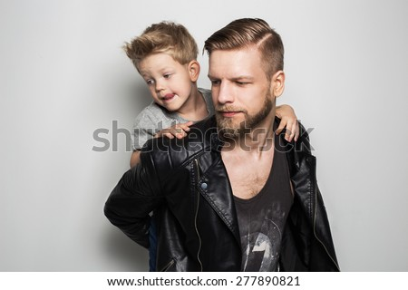 Portrait of young attractive smiling father playing with his little cute son. Fathers day.  Studio portrait over white background - stock photo