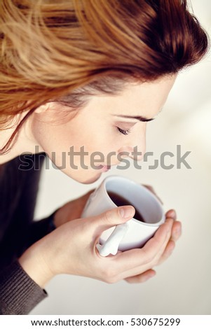 portrait of young attractive smiling woman with a cup of morning coffee or tea