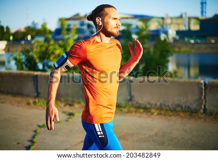 Portrait of young attractive sportsman running outside  - stock photo
