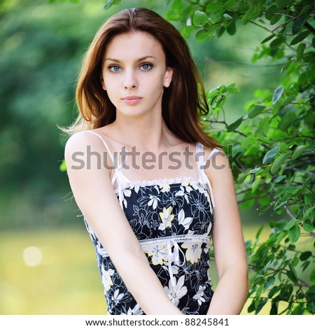 Portrait of young attractive woman at summer green park.