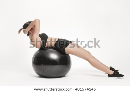 Portrait of young attractive woman doing exercises. Brunette with fit body exercising with fitness ball. Series of exercise poses. - stock photo