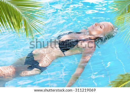Portrait of young attractive woman having good time in tropical pool