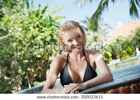 Portrait of young attractive woman having good time swimming pool