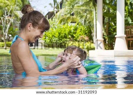 Portrait of young attractive woman having good time with her daughter - stock photo