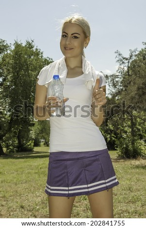 portrait of young attractive woman holding a bottle of water - stock photo