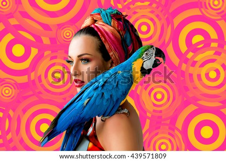 Portrait of young attractive woman in african style with ara parrot on her showlder on colorful background - stock photo