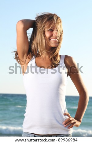 portrait of young attractive woman in black bikini on sky background - stock photo