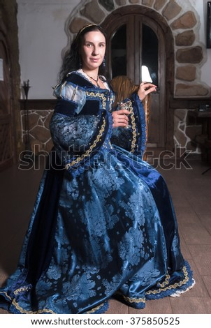 Portrait of young attractive woman in dress sits on chair of retro baroque style - stock photo