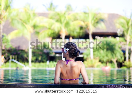 portrait of young attractive woman in luxury pool - stock photo