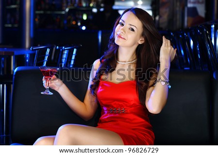 Portrait of young attractive woman in night club with a drink - stock photo