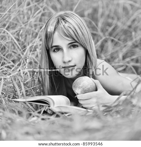 Portrait of young attractive woman lying in grass, reading book and holding apple at summer green park. - stock photo