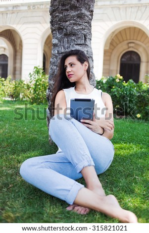Portrait of young attractive woman reading digital e-book on touch pad while sitting in the park on campus, lovely latin female using tablet computer while relaxing outdoors in summer day  - stock photo
