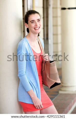 Portrait of young attractive woman smiling and leaning against wall with bag