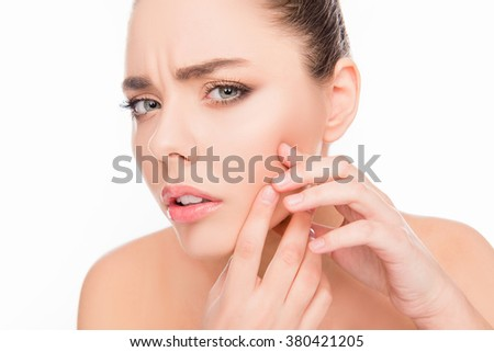 Portrait of young attractive woman touching her face and looking for acne - stock photo