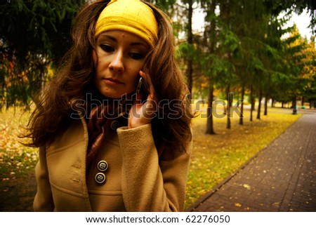 Portrait of young attractive woman walking outdoors in autumn park alley of fir trees - stock photo