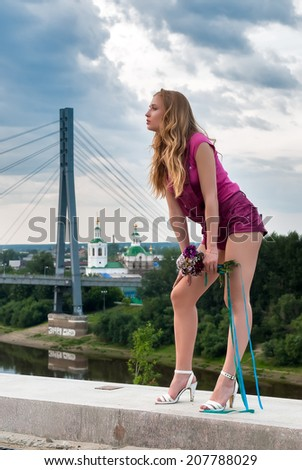 Portrait of young attractive woman with bouquet over city background - stock photo