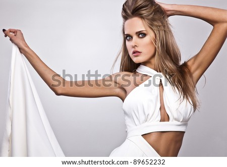 Portrait of young attractive woman with magnificent hair which posing in luxury silk dress.