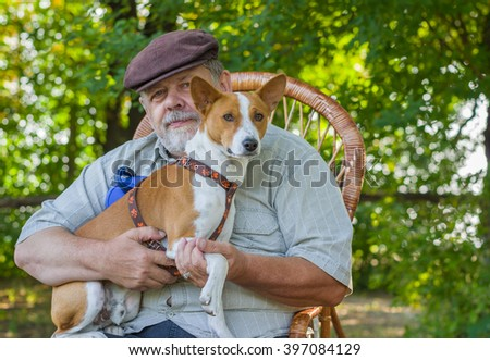 Portrait of young basenji and senior man sitting in a wicker chair in the park