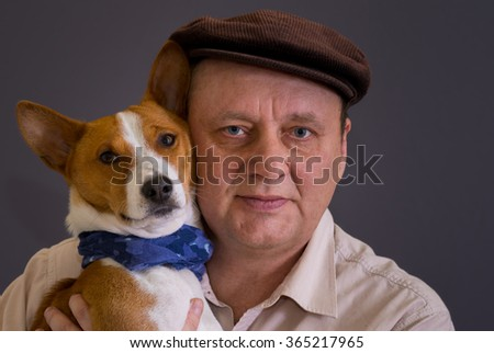 Portrait of young basenji dog wearing blue kerchief and its mature master wearing brown cap - stock photo