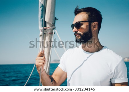 Portrait of young bearded man standing on a yacht and looking at the horizon. - stock photo