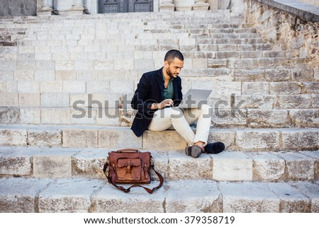 Portrait of young bearded man using his laptop while sitting on steps of city building - stock photo