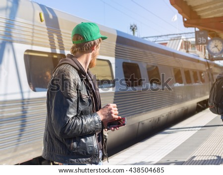 portrait of young bearded man waiting for train looking away on railway station in europe on sunny summer day, checking departure or arrival on his phone - stock photo