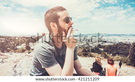 Portrait of Young Bearded Man Wearing Sunglasses and Smoking Cigarette at Scenic Overlook Above Mediterranean City of Athens on Sunny Day, Athens, Greece - stock photo