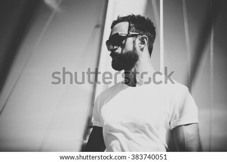 Portrait of young bearded man wearing sunglasses standing on the yacht in sunny day. Horizontal mockup, black and white - stock photo