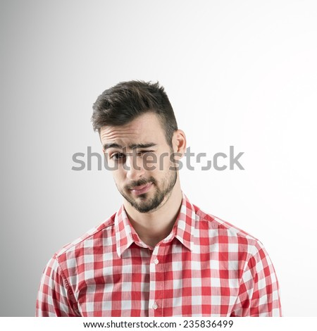 Portrait of young bearded man winking with his left eye over gray background.  - stock photo