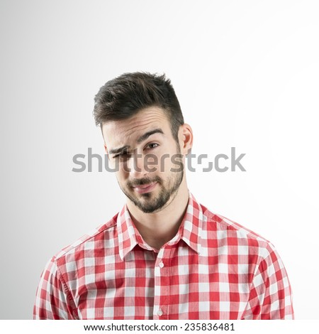 Portrait of young bearded man winking with his right eye over gray background.  - stock photo