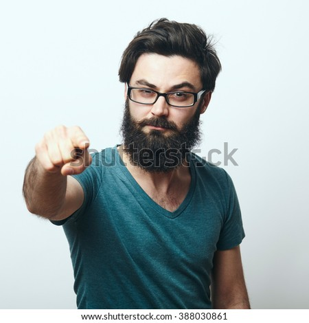 Portrait of young bearded man with glasses pointing his finger to the camera. We need you concept. Programmer, IT specialist pointing to camera. - stock photo