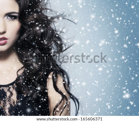 Portrait of young, beautiful and emotional brunette woman over blowing wind and snowy blizzard  - stock photo