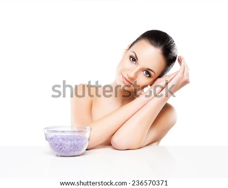 Portrait of young, beautiful and healthy woman with a mineral salt isolated on white - stock photo