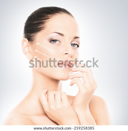 Portrait of young, beautiful and healthy woman with arrows on her face (spa, plastic surgery, face lifting and make-up concept) - stock photo
